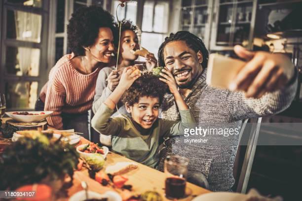 família feliz do americano africano que tem o divertimento ao tomar um selfie durante a refeição em casa. - african american family dinner - fotografias e filmes do acervo