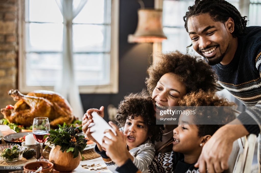 Happy African American family taking a selfie during Thanksgiving lunch. : Stock Photo