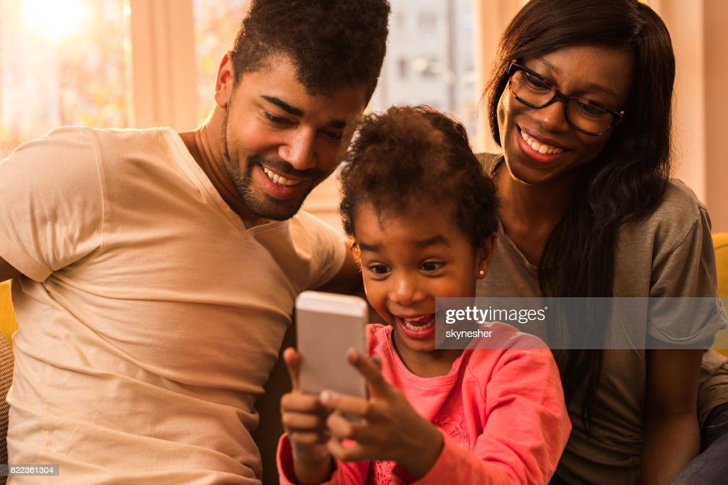 Happy African American family taking a selfie with mobile phone at home. : Stock Photo