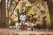 Happy African American family taking their dog for an autumn walk.