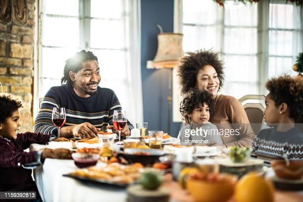 família feliz do americano africano que fala durante o tempo do almoço em casa. - african american family dinner - fotografias e filmes do acervo