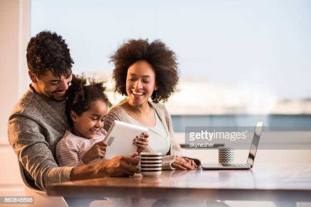 Happy African American family using wireless technology at home.