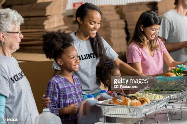 Happy African American family volunteer together in soup kitchen
