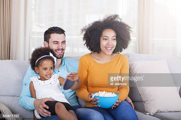 Happy African American Family watching TV and eating popcorn