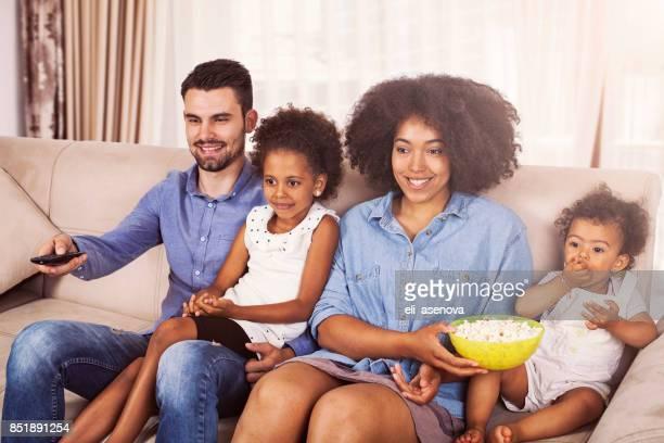 Glückliche afroamerikanischen Familie vor dem Fernseher und Essen popcorn