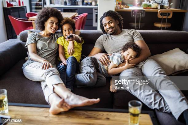 happy african american family watching tv in the living room. - watching tv stock pictures, royalty-free photos & images