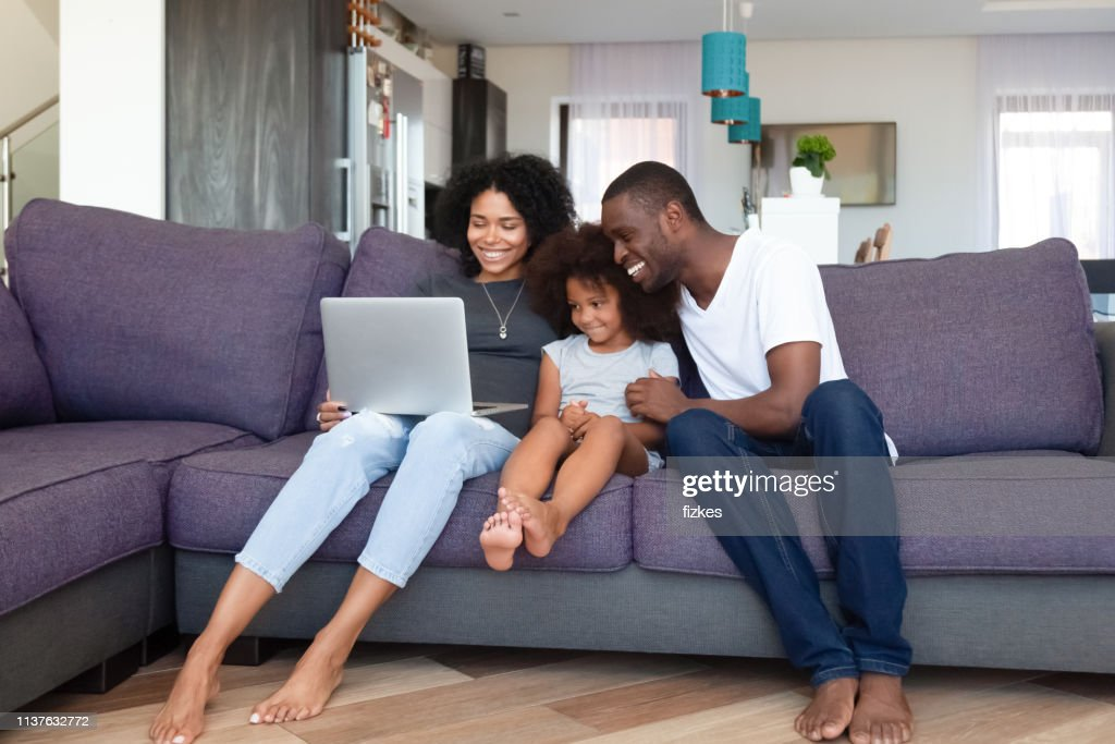 Happy African American family with daughter using laptop at home : Stock Photo