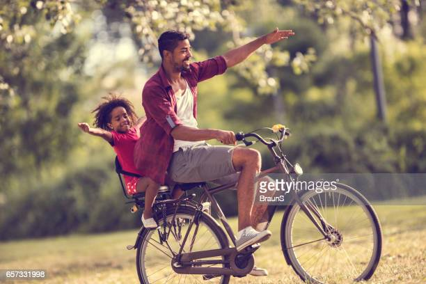 Happy African American father and daughter cycling in the park.