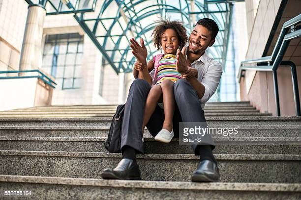 Happy African American father and daughter having fun on stairs.