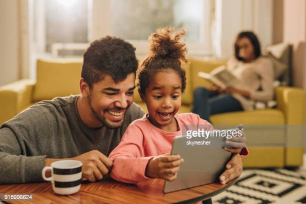 Happy African American father and daughter using digital tablet at home.
