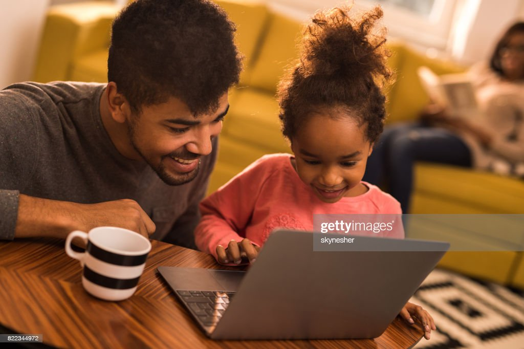 Happy African American father and daughter using laptop at home. : Stock Photo