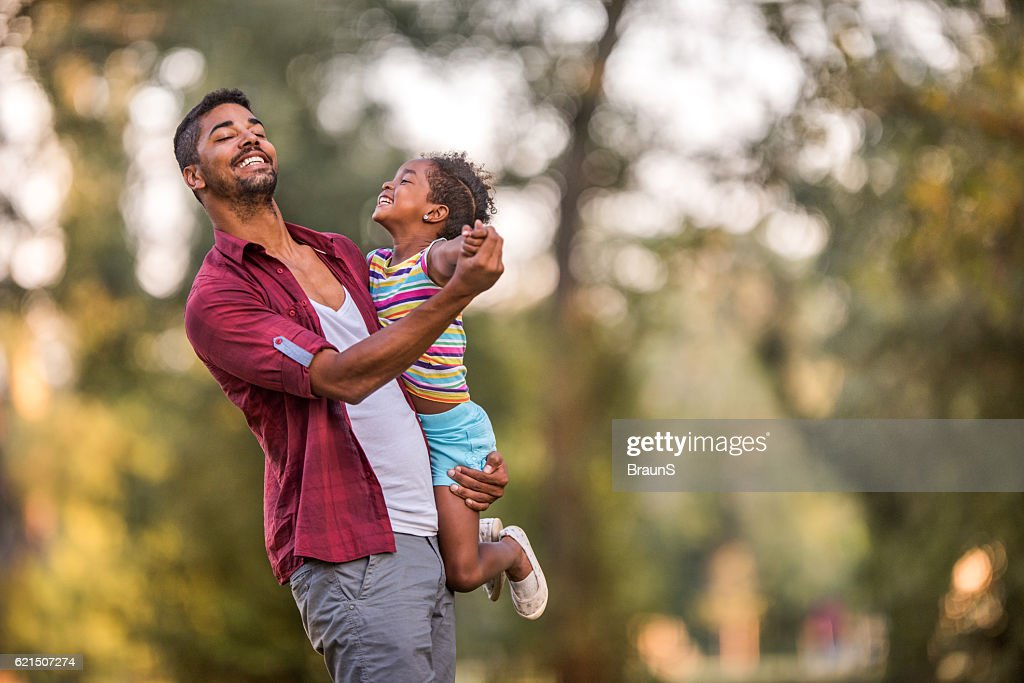Happy African American father dancing with his cute daughter outdoors. : Stock Photo