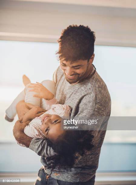 Happy African American father having fun while playing with his small daughter.