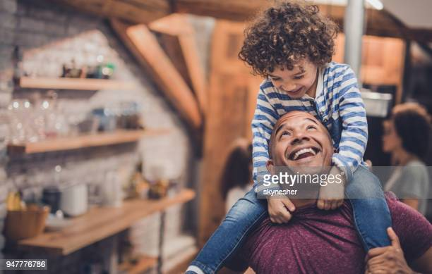 Happy African American father having fun with his boy while carrying him on shoulders at home.
