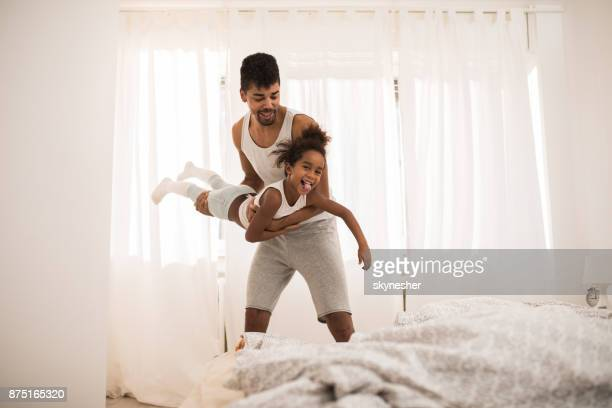 Happy African American father playing with his small daughter in the bedroom.