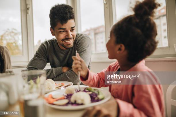happy african american father talking to his small daughter during lunch at home. - dining table stock pictures, royalty-free photos & images