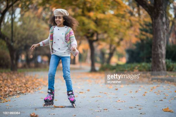happy african american girl having fun on her roller skates in the park. - inline skate stock photos and pictures