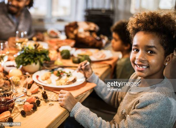 happy african american girl having lunch with her family in dining room. - black family dinner stock photos and pictures
