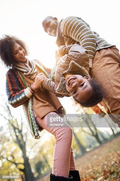 Feliz menina afro-americana a divertir-se com os pais ao ar livre.