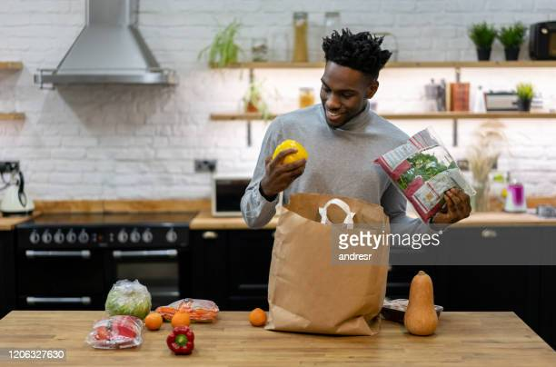happy african american man at home unpacking the groceries - unpacking stock pictures, royalty-free photos & images