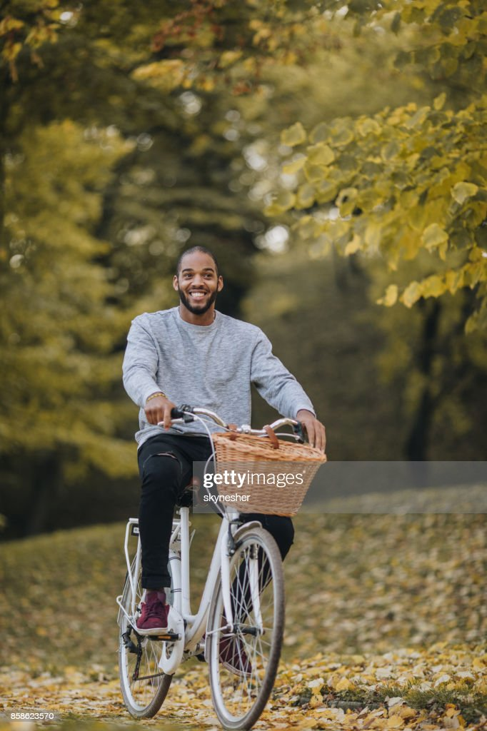 Afrikanischer Amerikaner glücklich durch den herbstlichen Park Radfahren. : Stock-Foto