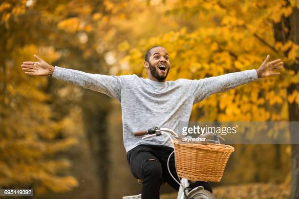 Happy African American man having fun while cycling with his arms outstretched in autumn day.