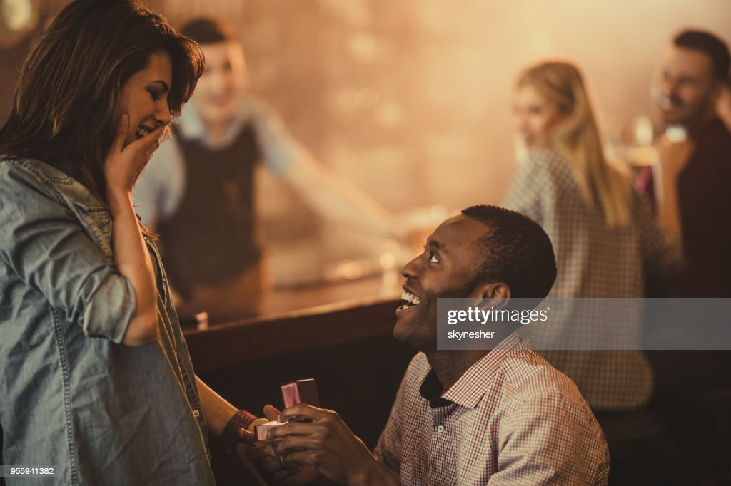 Happy African American man proposing to his girlfriend in a bar. : Stock Photo