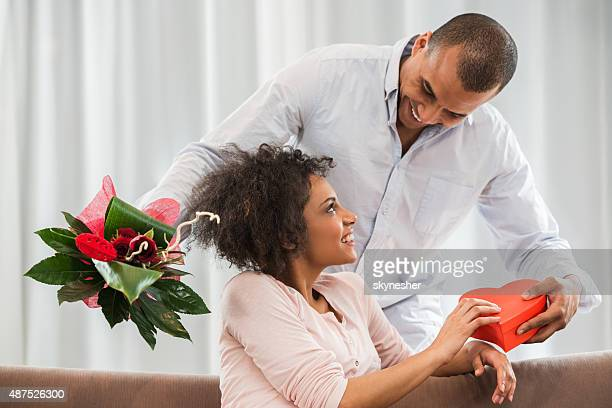 happy african american man surprising his wife for their annivesary. - valentines african american stock pictures, royalty-free photos & images