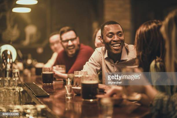 Happy African American man talking to his friend during the night out in a pub.