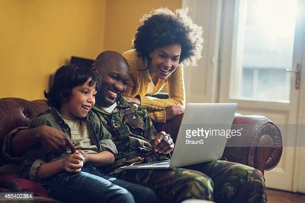 Happy African American military family using laptop at home.