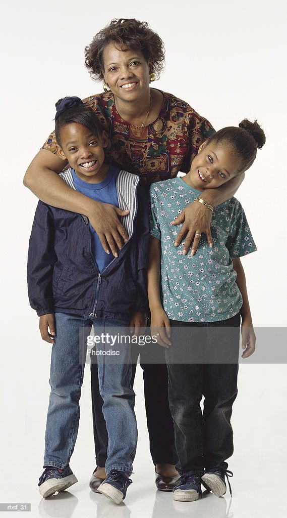 happy african american mom stands behind her two daughters : Stockfoto