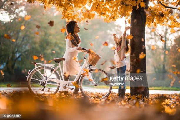 happy african american mother and daughter enjoying among autumn leaves at the park. - autumn falls stock pictures, royalty-free photos & images