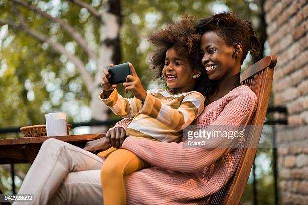Happy African American mother and daughter taking a selfie outdoors.