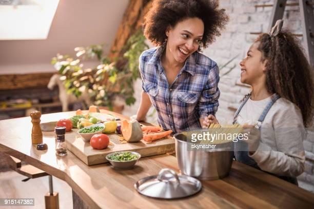 feliz mãe afro-americana e filha falando ao mesmo tempo fazendo o almoço juntos. - espaguete - fotografias e filmes do acervo