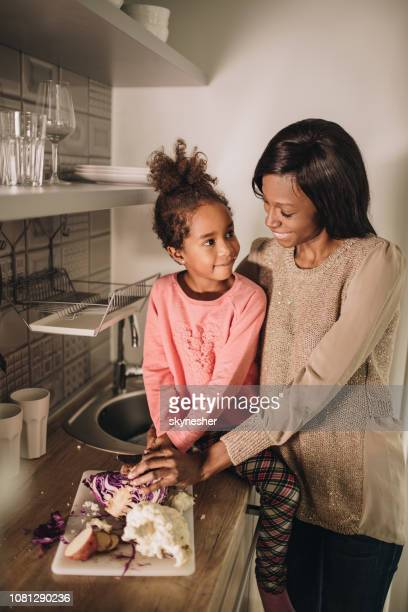 Happy African American mother and daughter talking while preparing food in the kitchen.