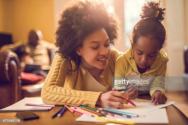 happy african american mother assisting her daughter in coloring. - colouring stock pictures, royalty-free photos & images