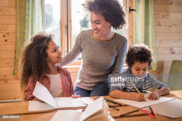 Happy African American mother assisting her small kids with drawing at home.