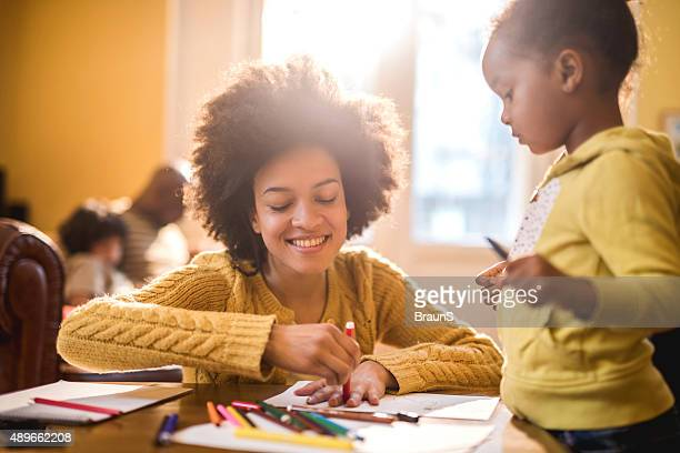 Happy African American mother drawing with her little girl.