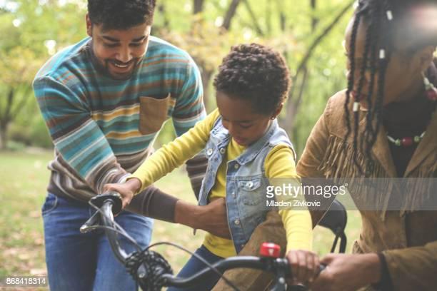 happy bike-afroamerikanische eltern unterrichten ihr kleines mädchen zum fahren im park. - pedalantrieb stock-fotos und bilder