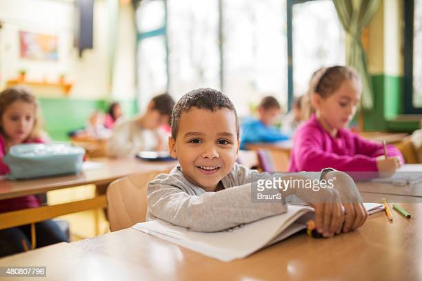 Happy African American schoolboy during a class in the classroom.