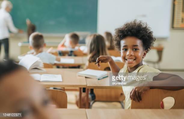 feliz aluna afro-americana em uma aula olhando para a câmera. - education - fotografias e filmes do acervo