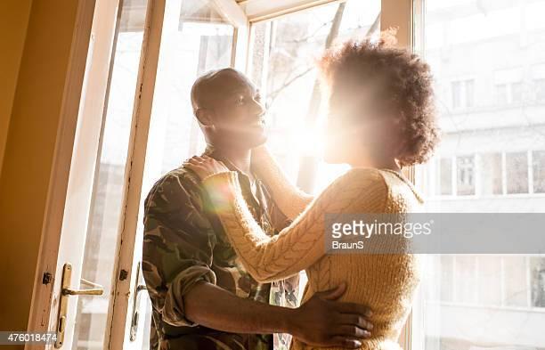 Heureux afro-américain soldier rentrer à la maison à sa femme.