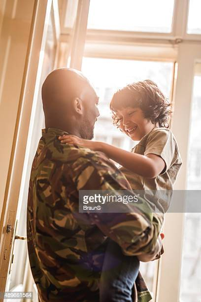 Happy African American soldier talking to his son at home.
