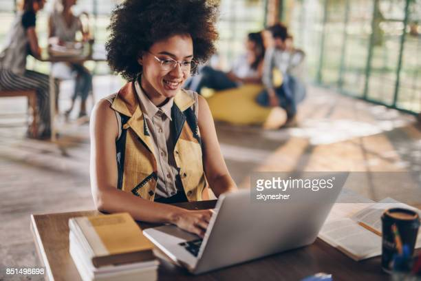 Happy African American student studying while using laptop.