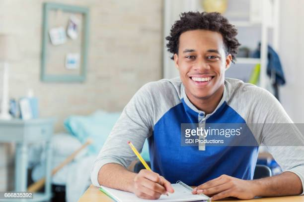 happy african american student works on homework - handsome black boy stock photos and pictures