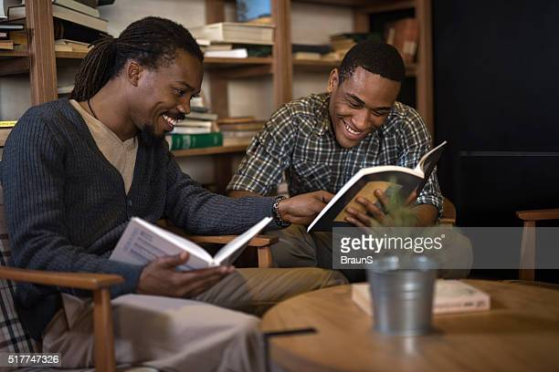 Happy African American students studying together in library.