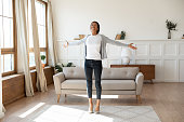 Happy african American woman dancing at home in living room