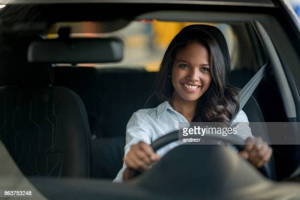 Happy African American woman driving a car