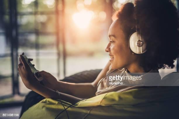 Feliz mujer afroamericana disfruta de buena música de teléfono celular.