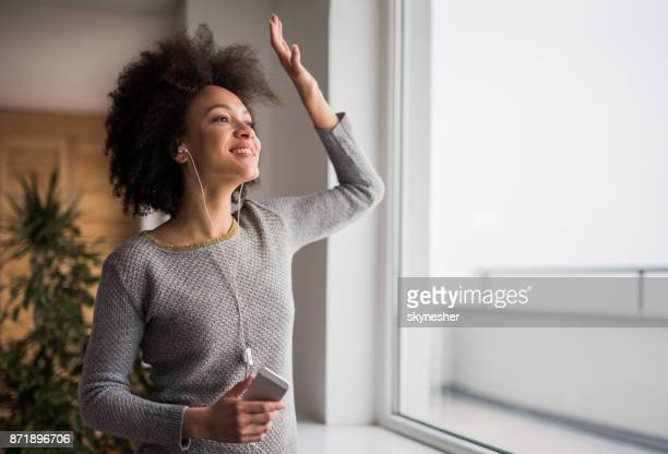 Happy African American woman enjoying while listening her favorite songs over smart phone.